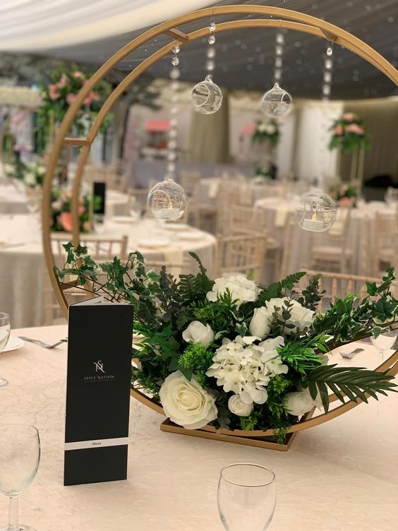 a double hoop wedding centerpiece with greenery, white blooms and hanging mini candleholders is a chic modern idea