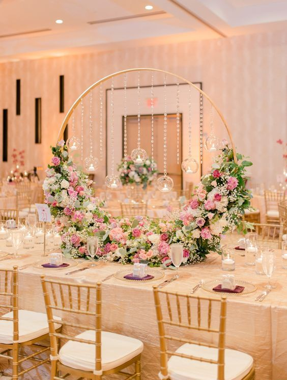 a formal and refined hoop wedding centerpiece with white, pink, light pink blooms, with candles hanging over the florals