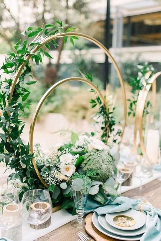 a gorgeous double hoop wedding centerpiece with greenery, white blooms and foliage is very ethereal and romantic
