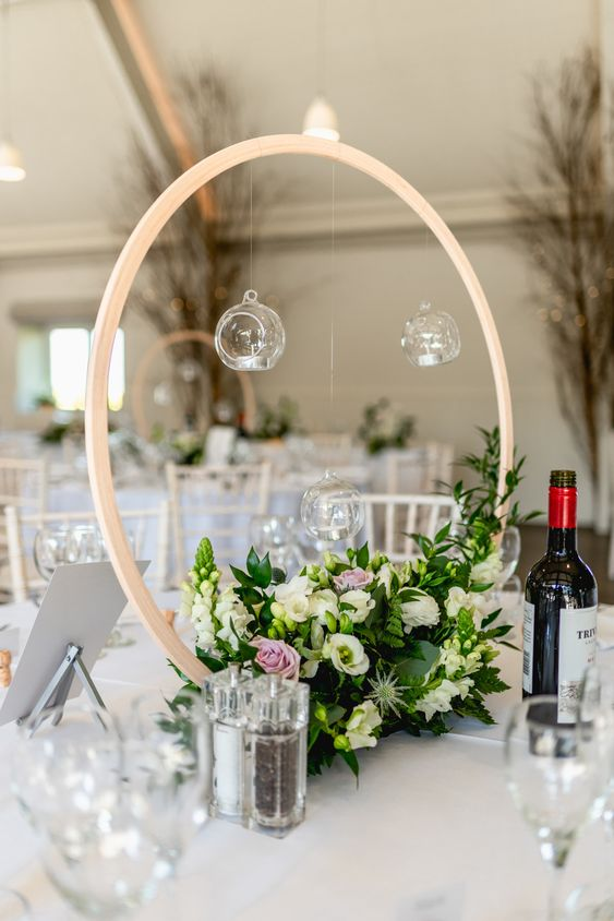 a hoop wedding centerpiece with greenery, white and pink blooms and candles hanging over the florals