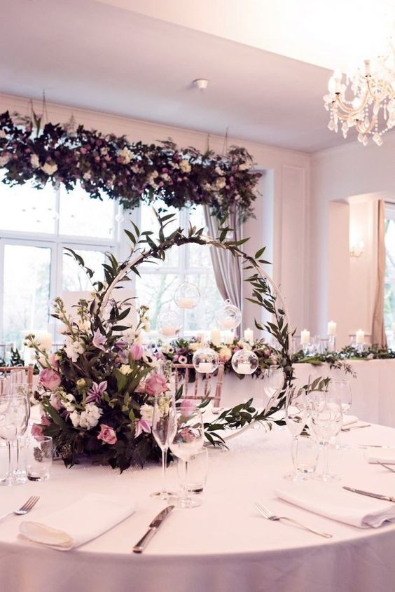 a hoop wedding centerpiece with greenery, white and pink blooms, candles hanging over the florals