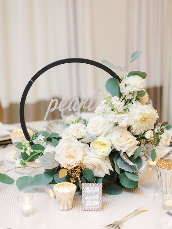a hoop wedding centerpiece with white blooms, greenery and a calligraphy topper and candles around