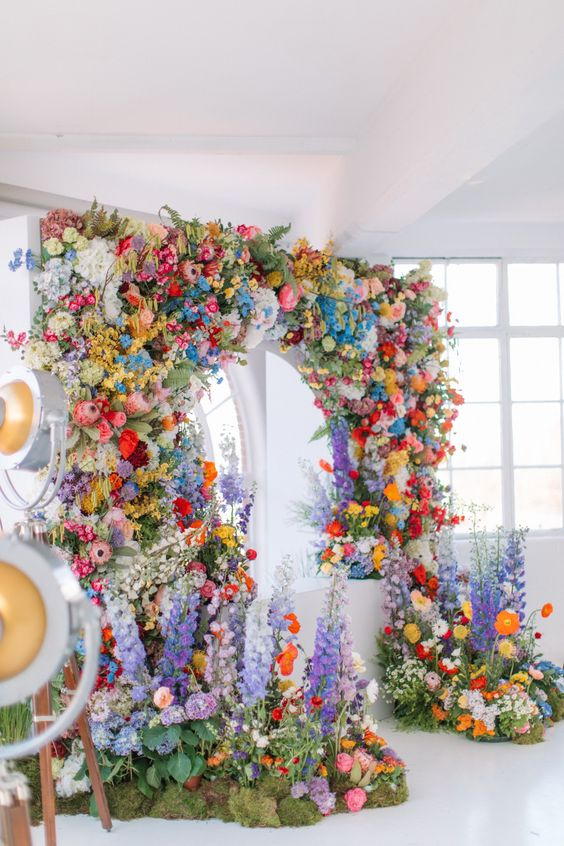 a jaw-dropping wedding arch of all kinds and colors of blooms and some foliage and moss is a fantastic idea for a wedding