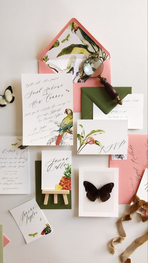 a jungle-themed wedding invitation suite with bright tropical prints, green and pink envelopes is a very cool idea