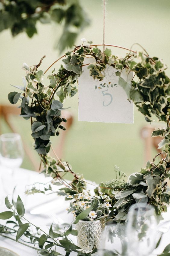 a lovely and airy double hoop wedding centerpiece covered with greenery and with a table number is a chic and fresh idea