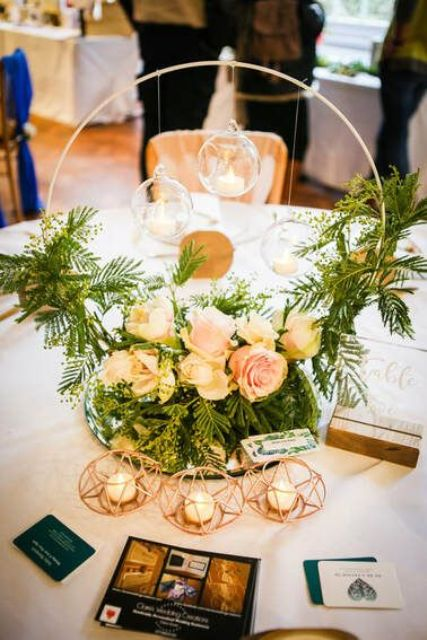 a lovely hoop wedding centerpiece with greenery and blush blooms, hanging candles over the florals and in geo candleholders
