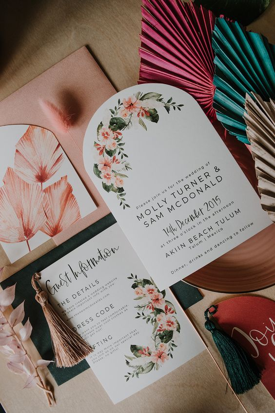 a lovely pastel tropical wedding invitation suite with floral, botanical prints and pink fronds plus cool letters