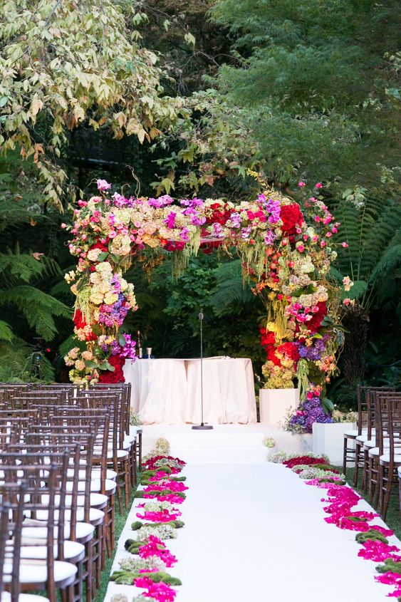 a lush and colorful floral wedding arch with greenery and bold blooms of various kinds for a bright and fun wedding
