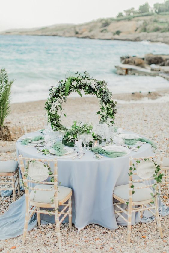 a lush greenery hoop wedding centerpiece with white blooms is a stylish idea for a coastal wedding and it looks fresh