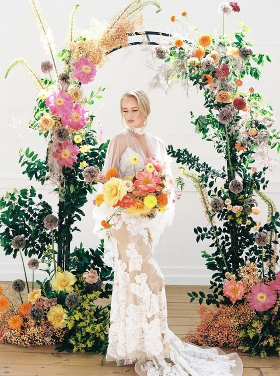 a modern refined wedding arch covered with greenery, with bold yellow, pink, orange and lilac blooms and herbs on top catches an eye