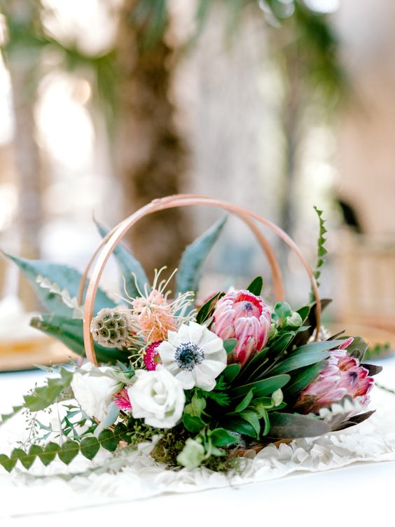 a pretty and bold double hoop wedding centerpiece with foliage and greenery, white blooms and pink proteas is a lovely idea