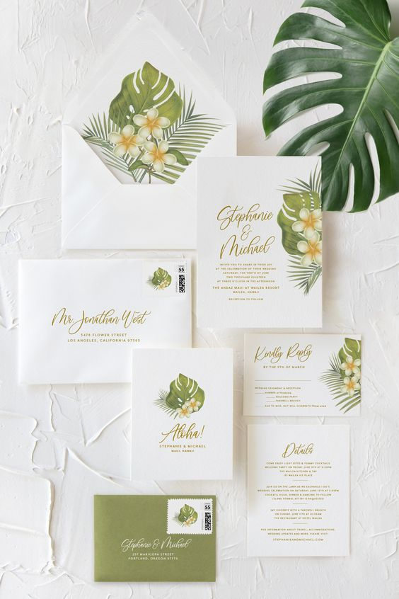 a pretty neutral tropical wedding invitation suite with tropical leaf and bloom prints is a very stylish and laconic option