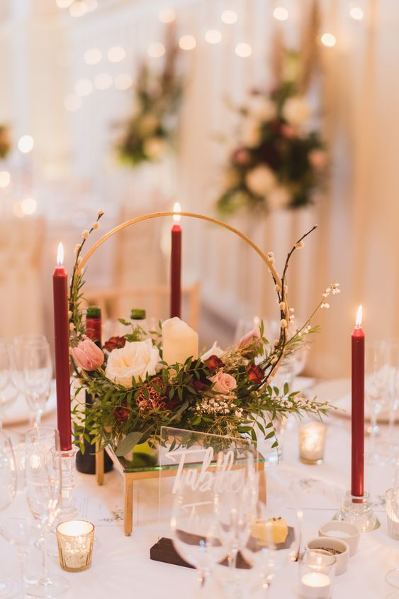a refined Christmas hoop wedding centerpiece with white, pink and burgundy blooms, red blooms around and small candleholders