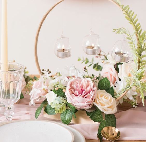 a refined and elegant hoop wedding centerpiece with blush, peachy blooms, greenery and candles hanging is pretty and chic
