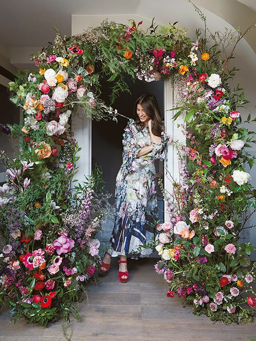 a refined floral wedding arch with much textural greenery and bold blooms plus herbs and twigs is a beautiful and chic idea