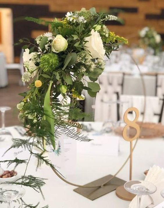 a refined hoop wedding centerpiece with greenery and white blooms plus a gilded table number for a chic wedding