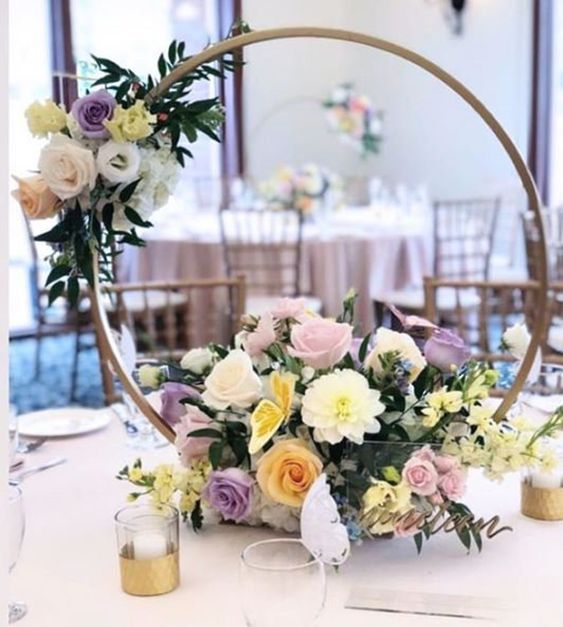 a romantic hoop wedding centerpiece of an embroidery hoop, with white, blush, yellow and lilac blooms and foliage