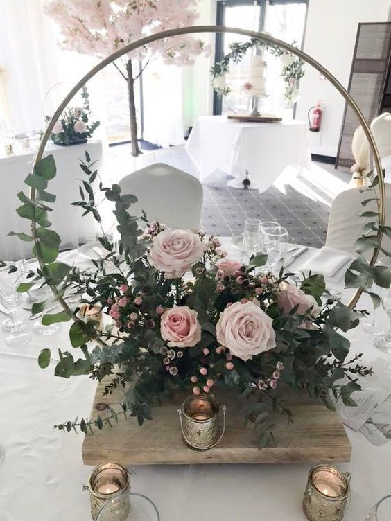 a romantic hoop wedding centerpiece with eucalyptus and lush light pink blooms plus candles around it