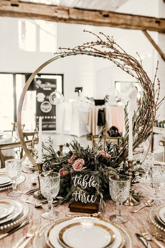 a romantic hoop wedding centerpiece with textural greenery, pink blooms and twigs going up the hoop plus a table number