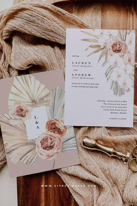 a romatic boho tropical wedding invitation suite with a blush envelope and tropical fronds and blooms prints