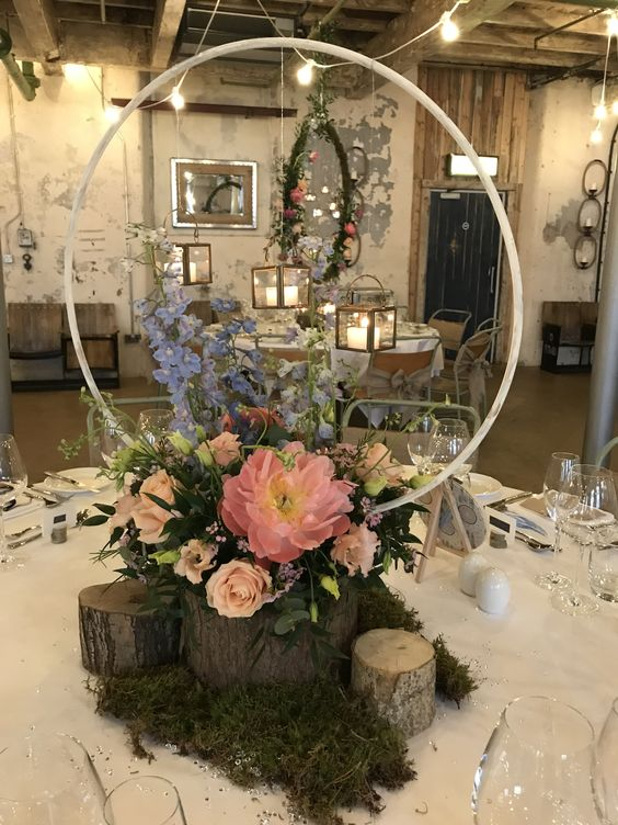 a rustic hoop wedding centerpiece with blue, blush and coral blooms placed on tree stumps and with moss around
