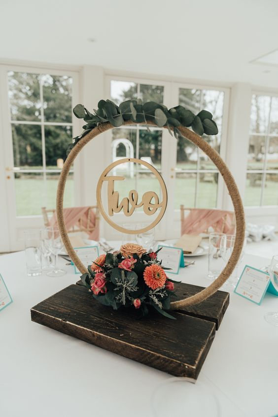 a rustic hoop wedding centerpiece with greenery, bright blooms and a table number plus a stained wooden platform
