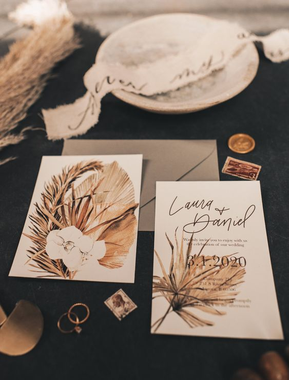 a stylish earthy tone wedding invitation suite with dried frond and orchid prints is a non-typical and cool idea