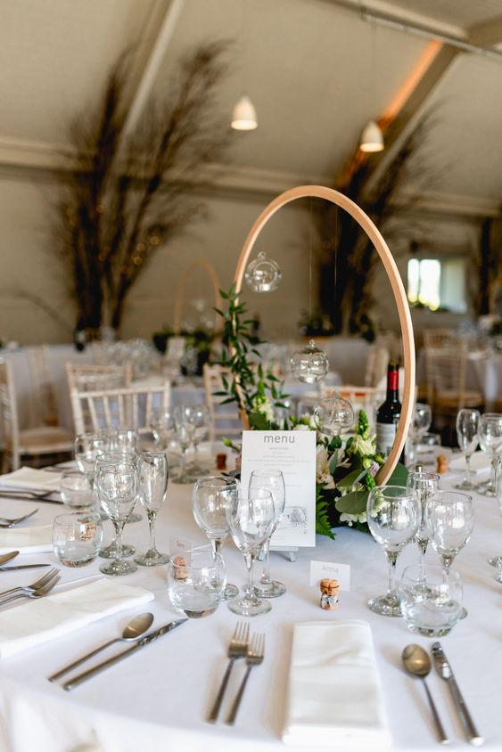a stylish hoop wedding centerpiece with greenery and white blooms plus candles hanging over the floral arrangement
