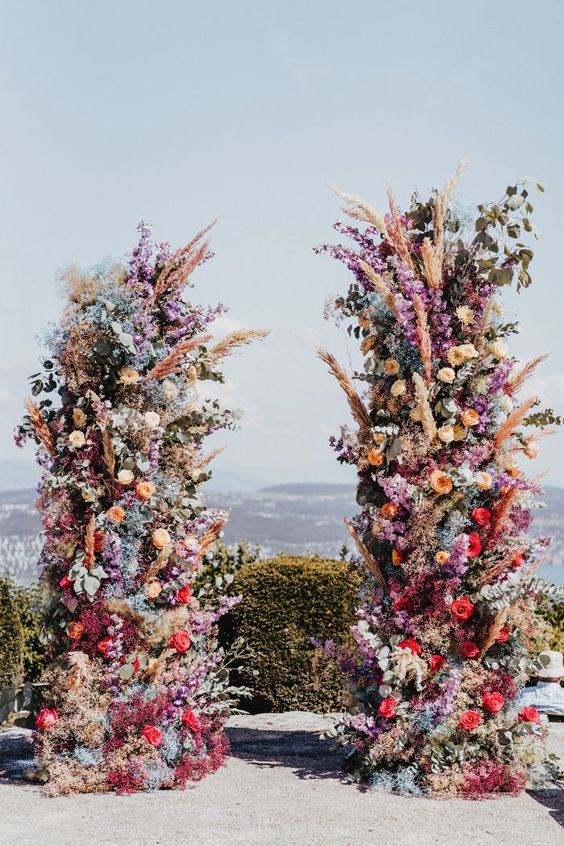a super bold and colorful floral wedding altar of red, orange, purple, blue and pink blooms, pampas grass and greenery for a statement