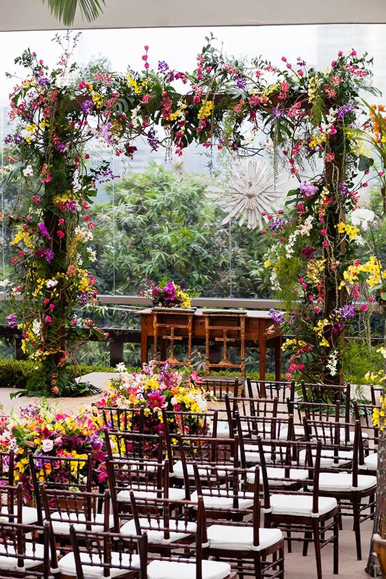 a super bright wedding arch covered with greenery, pink, purple, yellow, red blooms and blooming branches is amazing for a tropical wedding
