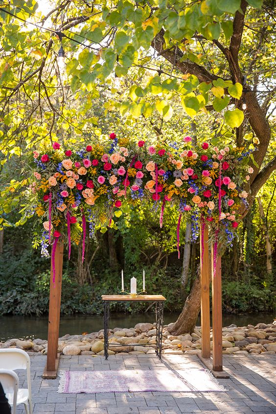 a super colorful wedding arch with greenery, red, pink, light pink, yellow and purple blooms is a lovely option for a summer wedding