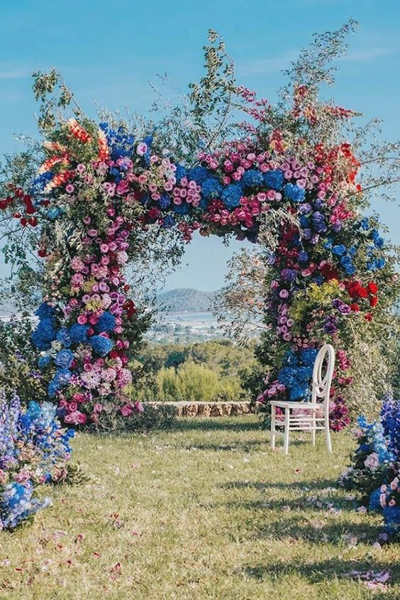 a super lush and bold floral wedding arch with blooming branches and flowers of all shades possible and with greenery