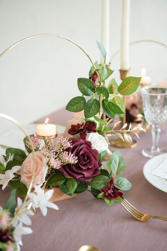 a trio of hoop wedding centerpieces with blush, white and burgundy blooms and greenery plus candles on a stand