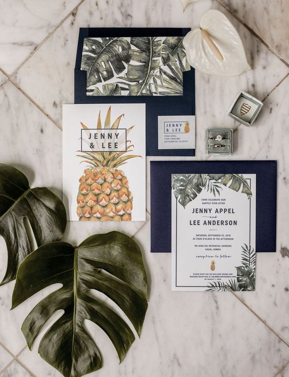 a tropical wedding invitation suite with navy envelopes, tropical leaf prints, pineapple prints and stylish lettering