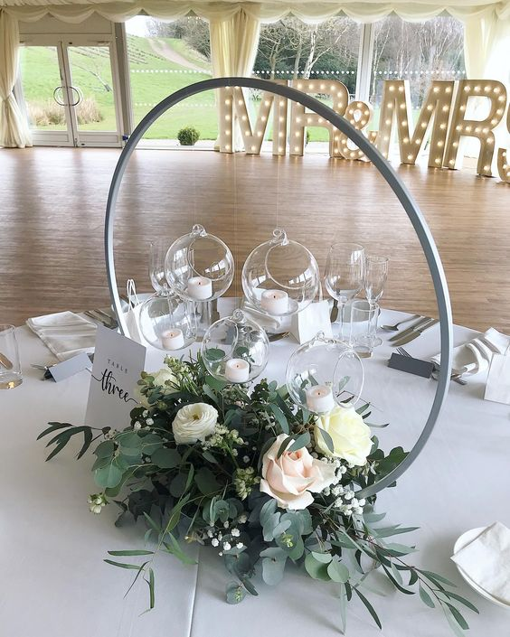 an elegant hoop wedding centerpiece with greenery and pastel arrangement, a card with a table number and some glass pendants with candles