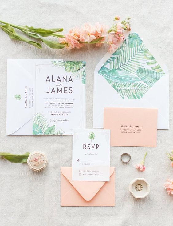 an elegant pastel wedding invitation suite with peachy pink envelopes, tropical leaf prints and black lettering