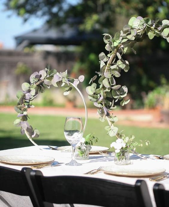 an ethereal embroidery double hoop wedding centerpiece covered with foliage is a lovely idea for a modern wedding