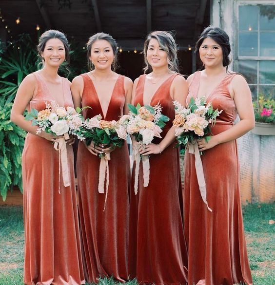 beautiful matching bridesmaid dresses in pink, peachy, orange and rust velvet, with deep necklines and thick straps are gorgeous