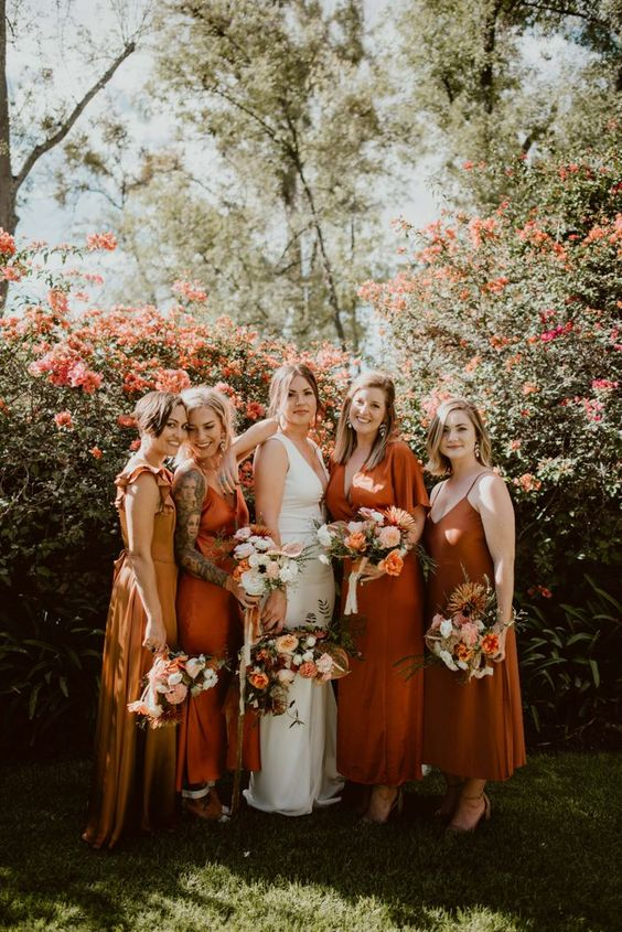 beautiful mismatching bridesmaid dresses - a yellow, orange ones and a rust one, midi and maxi for a trendy modern wedding