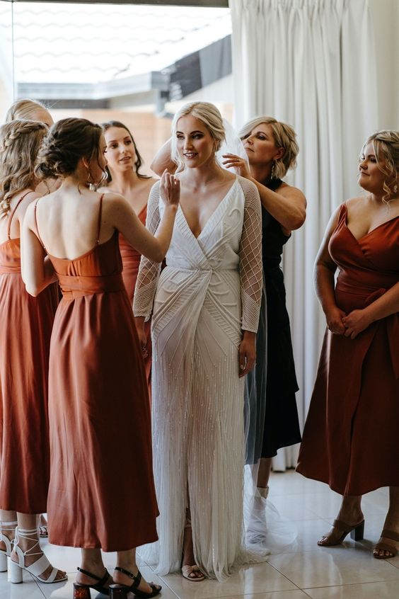 beautiful mismatching rust midi bridesmaid dresses with various necklines and looks plus mismatching heels for a trendy wedding