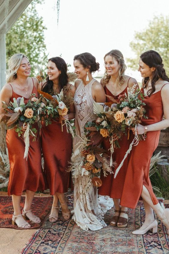 lovely and chic rust bridesmaid slip dresses of midi length and with side slits are very comfy to wear at any wedding
