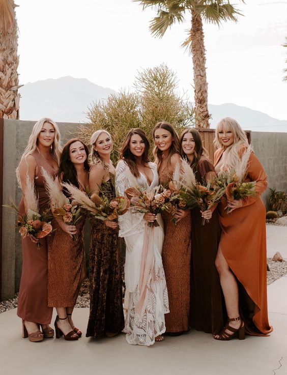 mismatching bridesmaid dresses in chocolate brown, orange, amber, with various necklines and looks for a boho wedding