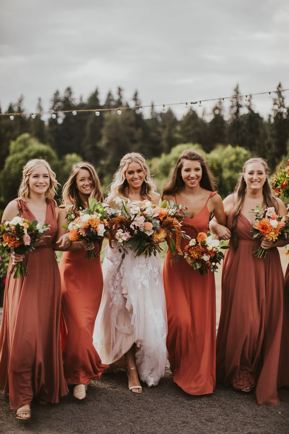 mismatching bridesmaid dresses in orange and rust, with mismatching necklines and detailing for great for a colorful fall wedding