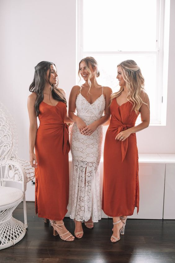 pretty burnt orange midi bridesmaid dresses with sashes, textural bodices and side slits plus neutral heels for a summer or fall wedding