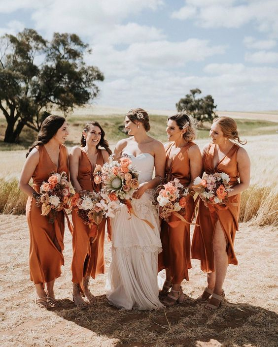 rust-colored midi bridesmaid dresses with tied up bodices and thick straps are an elegant option for many weddings