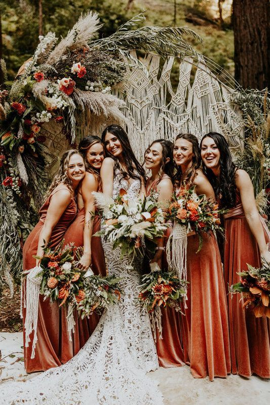 rust-colored velvet bridesmaid maxi dresses with mismatching necklaces are lovely for a boho wedding