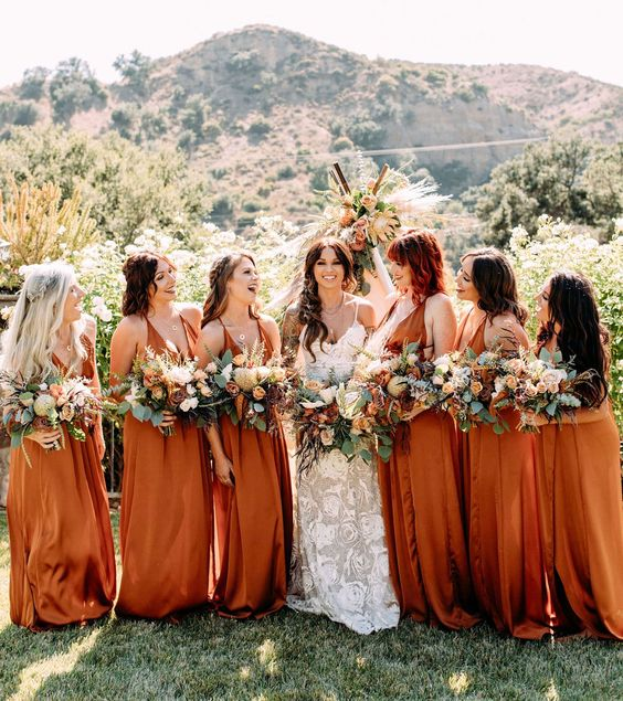 rust maxi bridesmaid dresses with deep necklines and thick straps are lovely for a summer or fall wedding