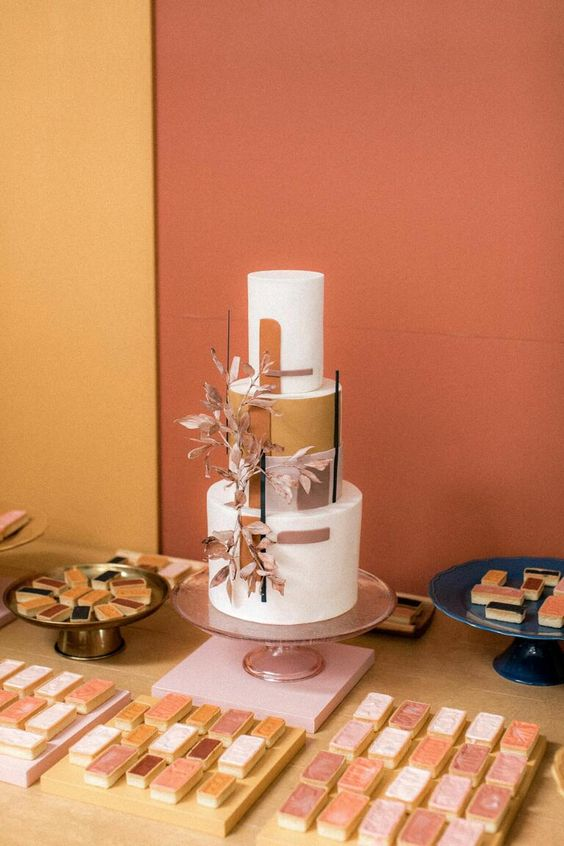 a 70s color block wedding cake with dried leaves and some lines and thin candles is a stylish idea for an earthy tone wedding