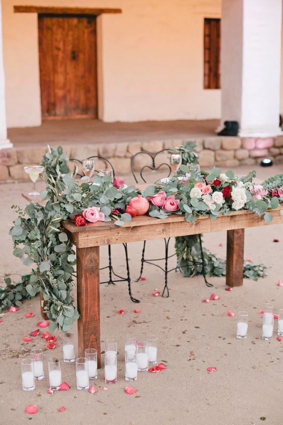 a beautiful and lush wedding table runner of eucalyptus, pink peonies, pink, burgundy and white roses and pomegranates for a spring or summer weddng