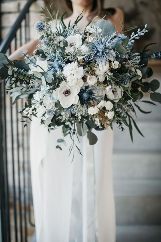 a beautiful wedding bouquet with white blooms, various types of greenery and thistles and allium is a gorgeous idea